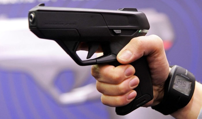 "An employee of Armatix poses for photographers as he presents the ÒSmartGun Concept""."